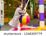 child jumping on colorful... | Shutterstock . vector #1268309779
