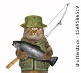 Stock photo the cat fisher in uniform is holding a big fish white background 1269586519
