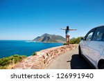 Small photo of carefree tourist stands on chapmans peak drive with arms outstretched in freedom girl pose with rental car