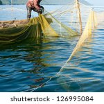 A Fisher On A Boat Hauls A Seine