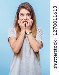 Small photo of Girl on blue background looks frightened. Concept of horror, fear, inevitable misfortune.Vertical.