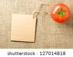 Photo of tomato vegetable and price tag on sacking background texture - stock photo