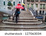 picture of a rainy day in Venice with an old bridge and crossing people with umbrellas - stock photo