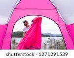 an asian man setting pink tent...   Shutterstock . vector #1271291539