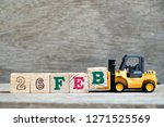 Toy forklift hold block B to complete word 26feb on wood background (Concept for calendar date 26 in month February)