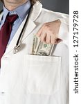Bribed doctor - doctor taking money into his pocket. Bribe and corruption in health and medicine industry. - stock photo