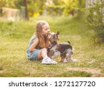 Stock photo cute little child girl sitting on the grass with her little yorkshire terrier dog in the park 1272127720