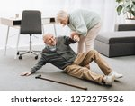 old woman helping to stand up... | Shutterstock . vector #1272275926