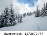 snowy fir forest on a hillside. ... | Shutterstock . vector #1272672499
