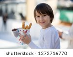 kid eating churros. sweet fried ... | Shutterstock . vector #1272716770