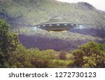 Unidentified flying object over a forest with trees and mountains behind. Old style photo with high ISO noise and dirt with scratches over time. 3D illustration. - stock photo