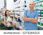 Stock photo man veterinarian with folder standing near shelfs with dry food in the pet store 1273264213