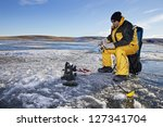 Man Ice Fishing On A Frozen...