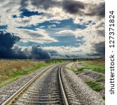 railroad to horizon and dramatic sky - stock photo
