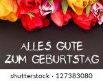Bunch of tulips with blackboard: happy birthday - stock photo