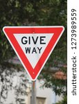 """Small photo of """"Give way"""" street signage indicating to drivers to give way ahead with trees in the background"""