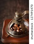 Old-fashioned handle coffee grinder with coffee beans on a dark wooden background close-up. - stock photo