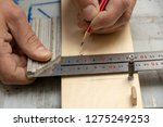 The furniture maker puts a marking on furniture preparation by means of a pencil and a joiner