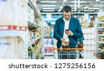 Small photo of At the Supermarket: Handsome Man Uses Smartphone and Takes Picture of the Can of Goods. He's Standing with Shopping Cart in Canned Goods Section.