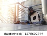 homeless man is sitting down on ... | Shutterstock . vector #1275602749