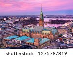 The Hamburg City Hall (German: Rathaus) with downtown and the lake Alster at dusk. Aerial view.