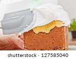 Spreading cream on christmas cake icing with spatula - stock photo
