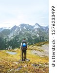 adventurer hiking in mountains... | Shutterstock . vector #1276233499