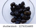 black olives in a glass bowl.... | Shutterstock . vector #1276316683