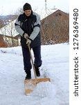 a man shovels snow from a... | Shutterstock . vector #1276369480