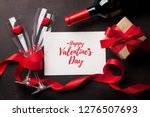 Stock photo valentine s day greeting card with red wine bottle and love gift box on stone background top view 1276507693