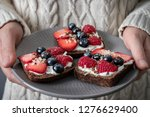 a person holds a plate with... | Shutterstock . vector #1276629400