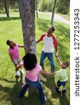 family in circle around tree in ... | Shutterstock . vector #1277253343