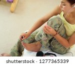 teenage girl sitting on bed... | Shutterstock . vector #1277365339