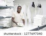 african male hotel worker folds ... | Shutterstock . vector #1277697340