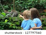 family looking at wild monkey... | Shutterstock . vector #127797560