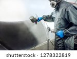 Mechanic wearing protective clothing holding a spray gun busy painting black paint on a vehicle hood. - stock photo