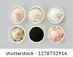 Small photo of Six assorted gourmet salts in bowls with black Hawaiian lava salt, Indus salt, Fleur de sel, rock salt and sea salt viewed from above