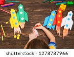 Small photo of preschool Child in creativity in the home. Happy kid makes rockets from paper. Children's creativity. Creative children play with craft. Tools and materials for children's art creativity on table.