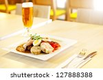 Small photo of Meat in sauce with heam, eggs and bread dumplings, in the background a restaurant out of focus