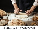 Small photo of Chef or baker, dressed in black apron, preparing a portion of fresh dough in rural bakery, kneading the pastry surrounded by rustic organic loaf of bread.