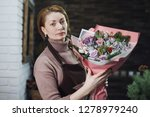 female florist in a brown apron ... | Shutterstock . vector #1278979240
