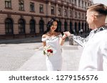 groom holds bride's arm while... | Shutterstock . vector #1279156576