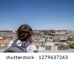 Woman tourist leans on ledge as she contemplates view of Jersalem, Israel