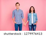 Stock photo portrait of nice charming lovely attractive cheerful confused couple holding hands looking at each 1279976413