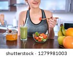 young woman eating salad on the ... | Shutterstock . vector #1279981003