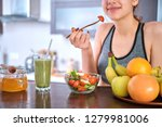 young woman eating salad on the ... | Shutterstock . vector #1279981006