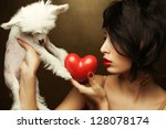 Portrait of a fashionable model with sexy red lips holding red heart (love symbol) and her gift: white little chinese crested dog. Both posing over golden background. Close up. Studio shot - stock photo