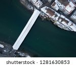 Aerial view Bird from above in Olten with old wooden bridge, city tower, railway station, openair pool, Jura mountains, Aare,  townhouse, St. Martins Church during Winter with snow on rooftops