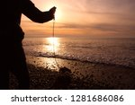 Stock photo a dog and dog walker at the beach at sunset 1281686086