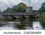 Old stone bridge over Glenarm River with ducks and castle tower, Glenarm, Northern Ireland